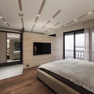Wysoka zabudowa w strefie sypialni z toaletką pełni funkcję garderoby. Przesuwne drzwi pokryte lustrem, dodatkowo powiększają przestrzeń. Projekt: Circle Huang&Gina Chiu. Fot. Hey! Cheese.