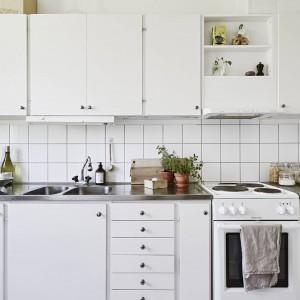 Kuchnię urządzono w typowej skandynawskiej stylistyce. Biała zabudowa wyposażona została w masę funkcjonalnych szuflad, a górne szafki pomieszczą wszelkie akcesoria i sprzęty. Fot. Stadshem.se/Janne Olander.