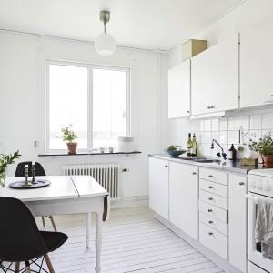 Dzięki zabudowie na jedną ścianę, w kuchni wygospodarowano miejsce na niewielki stolik jadalniany, przy którym stanęły easemowskie krzesła w czarnym kolorze, przebijającym dominację bieli. Fot. Stadshem.se/Janne Olander.