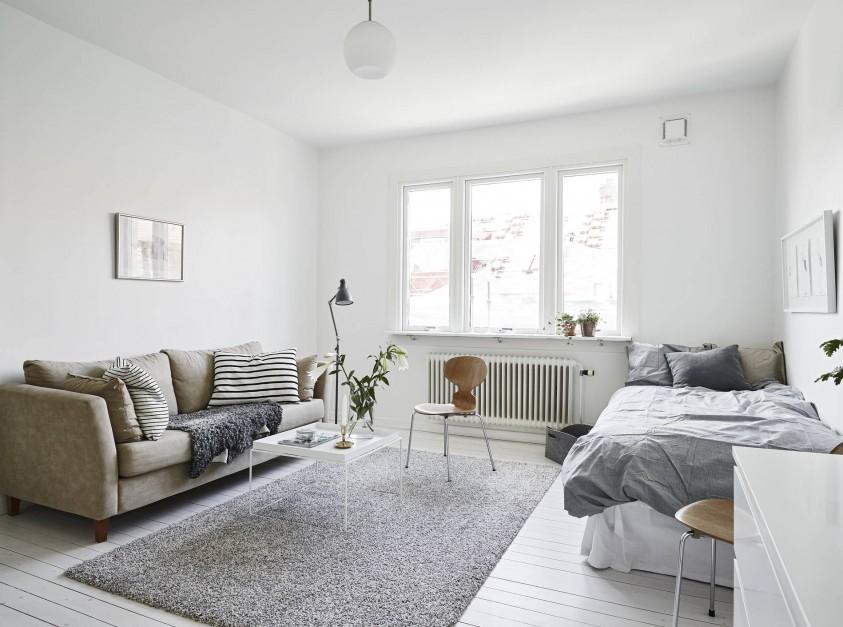 W niewielkim mieszkaniu salon połączono z sypialnią. Jedną strefę od drugiej umownie oddziela puszysty dywan położony w centrum pomieszczenia. Fot. Stadshem.se/Janne Olander.