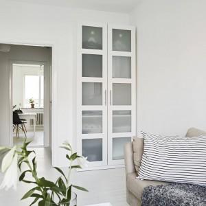 Białe są wszystkie elementy umeblowania w mieszkaniu - od zabudowy kuchennej po regał ze szklanymi witrynami w salonie. Fot. Stadshem.se/Janne Olander.