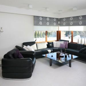 Chłodny, minimalistyczny salon urządzony został w bieli i czerni. Ten ponadczasowy duet barw uzupełniają neutralne szarości. Duży narożnik stanowi główne, choć nie jedyne wyposażenie. Projekt: Małgorzata Borzyszkowska. Fot. Bartosz Jarosz.