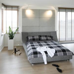 Betonowe płyty na ścianie za łóżkiem, w połączeniu z dużymi oknami, nadają przestronnemu wnętrzu loftowy charakter. Odrobinę przytulności wnosi podłoga z bielonego drewna. Projekt: Agnieszka Ludwinowska. Fot. Bartosz Jarosz.