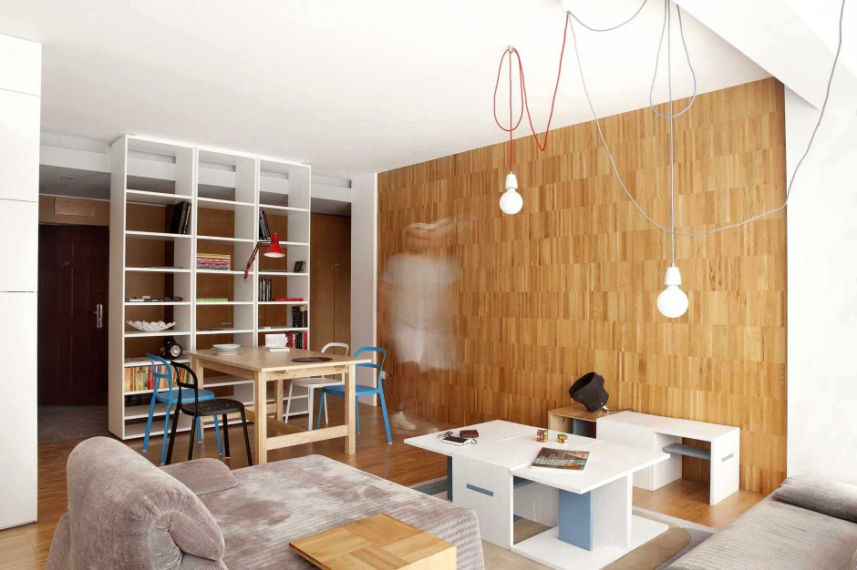 Płynne przejście parkietu z powierzchni podłogi na ścianę daje wrażenie przestrzeni oraz ociepla strefę dzienną skąpaną w bieli i szarościach. Projekt: Studio DontDIY. Zdjęcia: Asen Emilov, Ventsilsava Vasileva.