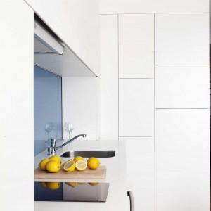 Zabudowa kuchenna z białego MDF-u, sięgająca od podłogi po sufit, z powodzeniem mieści zarówno naczynia i akcesoria, jak i zapasy żywności. Rozwiązanie bezuchytowe sprawia, że powierzchnia jest jednolita a przy tym elegancka. Projekt: Studio DontDIY. Zdjęcia: Asen Emilov, Ventsilsava Vasileva.