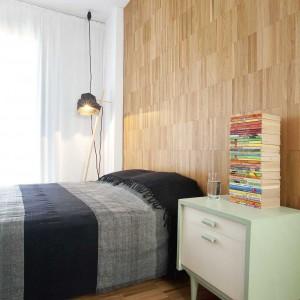 Ścianę za łóżkiem oraz podłogę, podobnie jak w salonie, wykończono panelami. W ten sposób wnętrze zyskało przytulny charakter sprzyjający wypoczynkowi. Projekt: Studio DontDIY. Zdjęcia: Asen Emilov, Ventsilsava Vasileva.