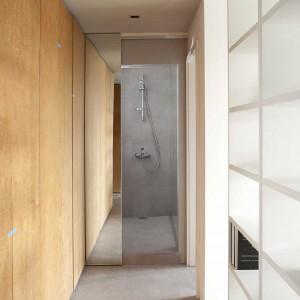 Na końcu korytarza zlokalizowano niewielką łazienkę. Ukryto ją za lustrzanymi drzwiami przesuwnymi, które optycznie powiększają toaletę i przedpokój. Projekt: Studio DontDIY. Zdjęcia: Asen Emilov, Ventsilsava Vasileva.