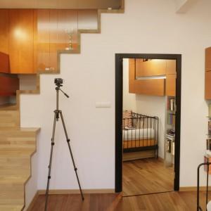Ciekawym rozwiązaniem architektonicznym są schody, prowadzące do szafek w górnej zabudowie. Wyłożone jasnym drewnem stopnie pełnią też rolę wystawy, na której eksponowane są trofea zdobyte przez gospodynię. Projekt: Michał Swałtek. Fot. Bartosz Jarosz.