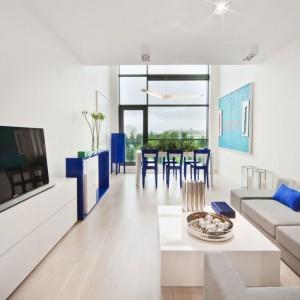 Wnętrze apartamentu urządzone zostało w powiększającej przestrzeń bieli. Ożywiają je kolorowe meble i dodatki. To bardzo odważne, ale i efektowne połączenie. Projekt: Maciej Zień. Fot. Ghelamco Poland.