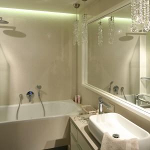 Na aranżację łazienki w stylistyce nowoczesnego glamour składają się m.in. dekoracyjne, kryształowe lampy oraz lustro w prostej białej ramie, które dodatkowo rozświetlają wnętrze. Projekt: Małgorzata Borzyszkowska. Fot. Bartosz Jarosz.