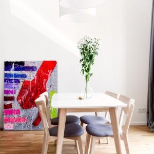 Jadalnia stanowi część salonu. Szarość krzeseł nawiązuje do tapicerki kanapy, a biały blat korespondujący z białymi lampami sprawia, że strefa spotkań przy wspólnym stole jest lekka i nowoczesna. Projekt: Olga Nowosad. Fot. Black Oak Studio.