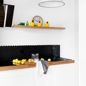 Monochromatyczną kuchnię ocieplona dębowym blatem urządzono jako odrębne pomieszczenie. Od strefy gościnnej oddziela ją ściana, przy której ustawiono telewizor. Projekt: Olga Nowosad. Fot. Black Oak Studio.