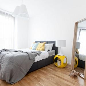 Spokojny klimat, jaki panuje w sypialni to zasługa bieli, czerni i szarości. Aby jednak wnętrze nie wydawało się nudne, aranżację przełamano żółtymi akcentami: oryginalnym stolikiem nocnym oraz poduszkami. Projekt: Olga Nowosad. Fot. Black Oak Studio.