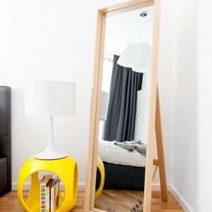 Nie lada ozdobę stanowi duże lustro ustawione w rogu sypialni, oprawione w ramę z litego drewna, nawiązującego barwą do deski podłogowej. Projekt: Olga Nowosad. Fot. Black Oak Studio.