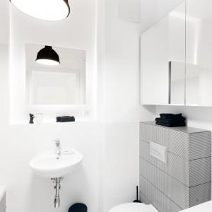 Aby nie przytłoczyć wnętrza zbyt dużą ilością wzorów, pepitkę umieszczono jedynie na obudowie stelaża WC oraz na froncie wanny. Projekt: Olga Nowosad. Fot. Black Oak Studio.