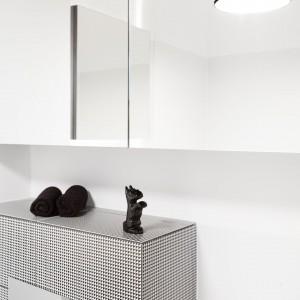 Nad stelażem WC na jego pełną szerokość umieszczona została kolejna półka z frontem lustrzanym. Taki celowy zabieg (połączenia szafki z lustrem) sprawia, że mamy dużo więcej miejsca do przechowywania w łazience niezbędnych kosmetyków czy środków czystości. Projekt: Olga Nowosad. Fot. Black Oak Studio.