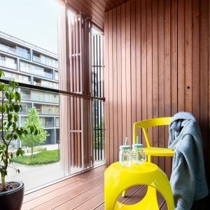 W ciepłe dni rolę strefy relaksu pełni duży balkon, wykończony drewnem, które nadaje mu naturalny, sprzyjający wypoczynkowi wygląd. Projekt: Olga Nowosad. Fot. Black Oak Studio.