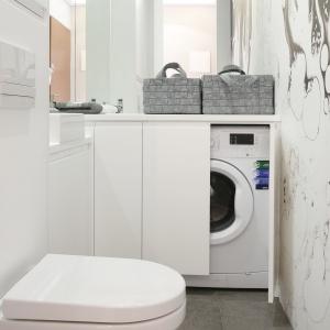 Umieszczona w głębi wąskiej łazienki zabudowa z MDF-u mieści pralkę, obok jest także miejsce na detergenty. Proj. Karolina Łuczyńska. Fot. Bartosz Jarosz.