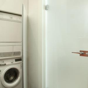 Pojemna zabudowa łazienkowa na całą szerokość i wysokość ściany mieści pralkę i suszarkę.  Proj. Michał Mikołajczak. Fot. Bartosz Jarosz.