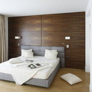 W sypialni dominuje drewno. Zdobi ono nie tylko podłogę, ale też ścianę za wezgłowiem łóżka. To ostatnie, ubrane w szarą tapicerkę, doskonale prezentuje się na takim tle. Projekt: Kamila Paszkiewicz. Fot. Bartosz Jarosz.
