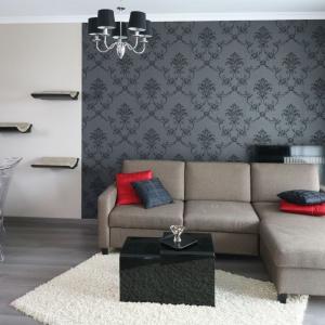 W niedużym mieszkaniu salon połączono z gabinetem. Przestrzeń wypoczynkową wyznacza elegancki narożnik ustawiony na tle ściany z tapetą w stylu glamour. Projekt: Joanna Nawrocka. Fot. Bartosz Jarosz.