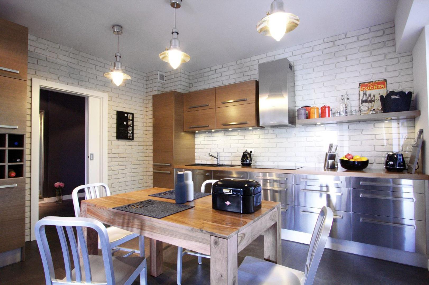 Część frontów zabudowy kuchennej wykonano ze stali, która nadaje przestrzeni surowy, industrialny klimat. Metalowe powierzchnie idealnie harmonizują z technicznym oświetleniem nad stołem. Projekt i zdjęcia: Soma Architekci.