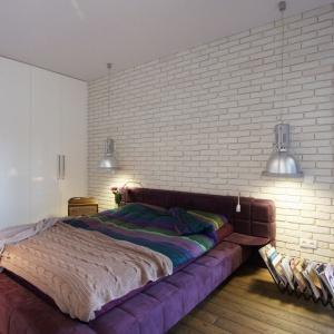 Podobną białą cegłą wykończono również ściany w sypialni. Z surową fakturą idealnie komponuję się dwie, metalowe lampy zawieszone po obu stronach łóżka, zastępujące tradycyjne lampki nocne. Projekt i zdjęcia: Soma Architekci.
