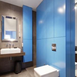 Mocnym, kolorystycznym akcentem, przebijającym stonowane szarości i brązy jest błękitna zabudowa wykończona na wysoki połysk. Jej kontrast widoczny jest nie tylko w intensywnej barwie, ale i w połyskującej fakturze, która przebija monotonię matowych powierzchni. Projekt i zdjęcia: Soma Architekci.