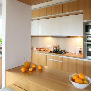 W tej pięknej kuchni dominuje kolorystyka ciepłego drewna, przełamanego śnieżną bielą. Górne szafki mają dwa rzędy - niższy i płytszy z białymi frontami, górny i głębszy (przy czym niższy) z frontami w kolorze dolnej zabudowy. Projekt: Marcin Lewandowicz. Fot. Bartosz Jarosz.
