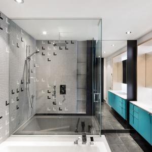 W łazience króluje szarość i proste kształty. Do kwadratowej wanny przylega przestronna strefa prysznica, przesłonięta przez czyste przeszklenia. Całość ożywiają turkusowe fronty szafki podumywalkowej.  Projekt: Nature Humaine. Fot. Adrien Williams.