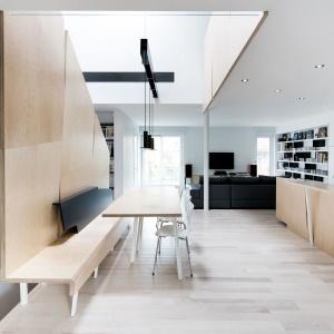 W dalszej części domu znalazł się przestronny salon, którego obecność akcentują ciemne meble wypoczynkowe, kontrastujące z białymi ścianami i jasną drewnianą podłogą. Projekt: Nature Humaine. Fot. Adrien Williams.