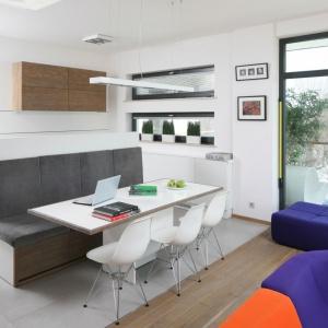 W przeciwieństwie do kolorowego salonu, kuchnia jest całkowicie biała. Ocieplają ją jedynie drewniane elementy aranżacyjne, dawkowane jednak z umiarem. Projekt: Konrad Grodziński. Fot. Bartosz Jarosz.