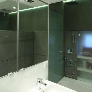 Mała łazienka dla rodziny urządzona została w szarościach. Okładziny ścian imitują betonowe płyty. Proj. Marcin Lewandowicz. Fot. Bartosz Jarosz.
