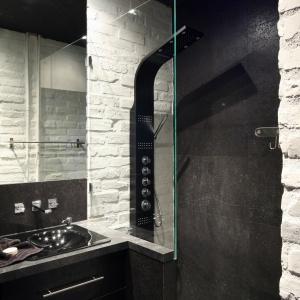Niewielka ścianka oddziela strefę umywalki od otwartej strefy prysznica. Cegła na ścianach podkreśla loftowy styl wnętrza. Proj. Dominik Respondek. Fot. Bartosz Jarosz.