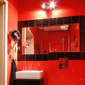 Mała łazienka została urządzona  w odważnej czerwieni. Lustro na całą ścianę dodaje wnętrzu optycznej przestrzeni.  Proj. Beta Ignasiak. Fot. Bartosz Jarosz.
