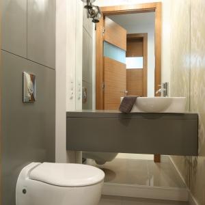 Mała i wąska toaleta jest urządzona elegancko i praktycznie. Miejsce nad obudową stelaży spłuczki wykorzystano na szafki. Proj. Małgorzata Galewska. Fot. Bartosz Jarosz.