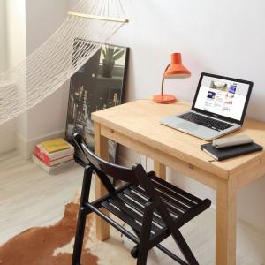 Niewielki stolik pełni funkcję biurka, ale może szybko przemienić się w jadalnię dla dwóch osób. Blat mebla się bowiem rozkłada. Projekt: Szymon Hanczar. Fot. Jędrzej Stelmaszek.