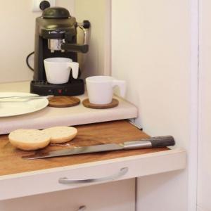 Z uwagi na bardzo ograniczoną przestrzeń, nie było możliwości zmieszczenia w małej kuchni dużego blatu kuchennego. Część powierzchni roboczej chowa się zatem w górnej szufladzie. Projekt: Szymon Hanczar. Fot. Jędrzej Stelmaszek.