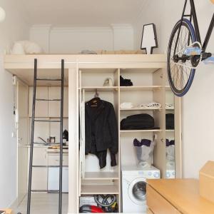 Na ścianie zamykającej kubik, w który wpasowano łazienkę urządzono szafę z licznymi półkami oraz wnęką na AGD. Projekt: Szymon Hanczar. Fot. Jędrzej Stelmaszek.