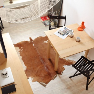 Przytulność we wnętrzu buduje drewno w przyjemnym, jasnym wybarwieniu oraz młodopolska skóra na podłodze. Projekt: Szymon Hanczar. Fot. Jędrzej Stelmaszek.