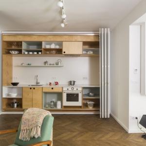 Meble kuchenne wykonane z drewna przełamują chłodną biel ścian. Drewno daje poczucie przytulności wnętrza oraz ciepło aneksu. Projekt: dontDIY. Fot. Asen Emilov.