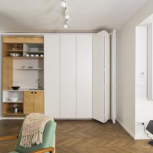 W razie potrzeby domownicy mogą w szybki i prosty sposób zamknąć kuchnię za białymi frontami, które harmonizują z resztą ścian, tworząc uporządkowaną aranżację. Projekt: dontDIY. Fot. Asen Emilov.