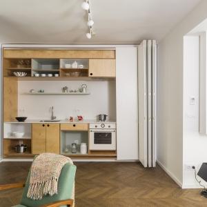 Pomysł na schowanie mebli kuchennych za białymi, przesuwnymi drzwiami pozwala właścicielom na ukrycie wszystkiego, co mniej istotne. Projekt: dontDIY. Fot. Asen Emilov.