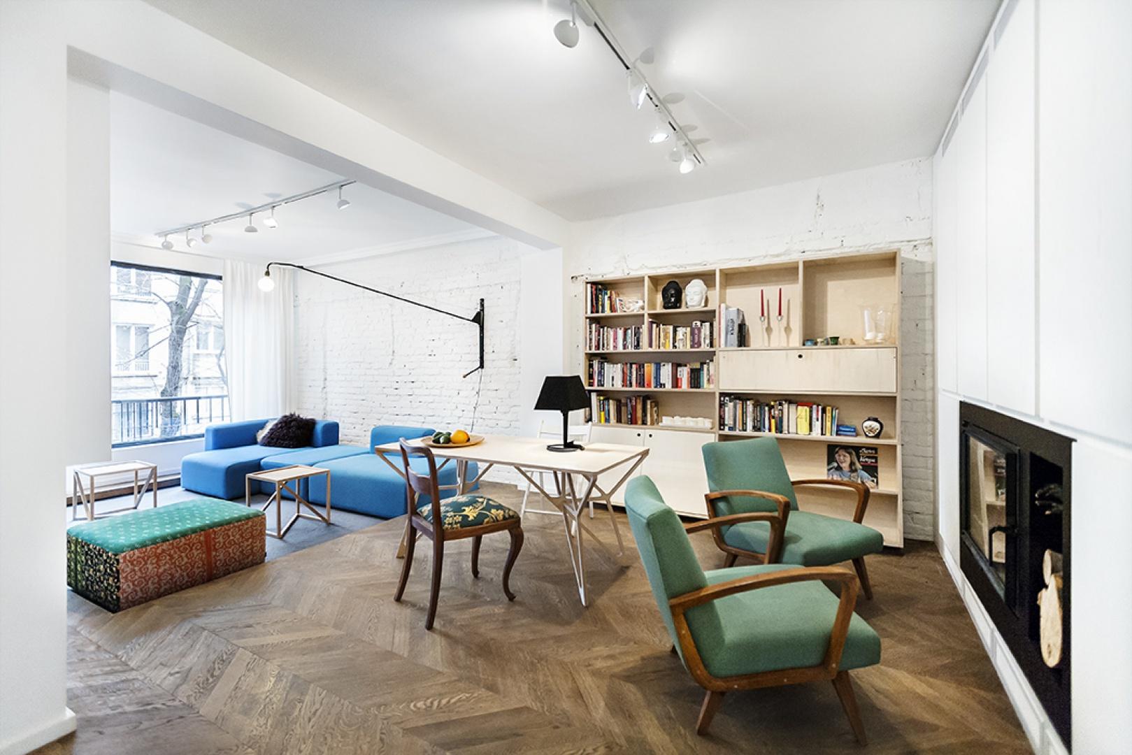 Jadalnia i salon posiadają wiele cech wspólnych. Spaja je wizualnie białą cegła na ścianie i drewniana podłoga. Projekt: dontDIY. Fot. Asen Emilov.