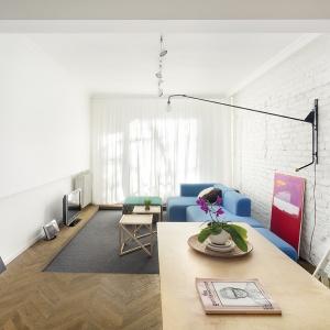 Duże salonowe okno wprowadza ogrom naturalnego światła, przez co wnętrze jest bardzo jasne. Biel na ścianach pogłębia te zjawisko przez co pomieszczenie zyskuje na przestronności. Projekt: dontDIY. Fot. Asen Emilov.
