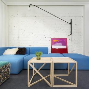 Przepiękna, błękitna kanapa w salonie stanowi centrum całej strefy dziennej. Pięknie prezentuje się na tle białej cegły na ścianie. Projekt: dontDIY. Fot. Asen Emilov.