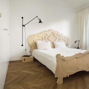 Drewniane łózko swoimi kształtami w postaci barokowej roślinności tworzy z bielą ścian podkreślenie naturalności sypialni oraz całego apartamentu. Projekt: dontDIY. Fot. Asen Emilov.