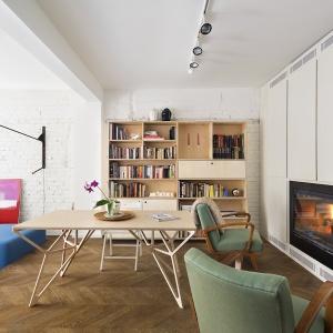 Stół o nieregularnych kształtach nóg tworzy nowoczesne zacięcie w stosunku do tradycyjnych foteli i kominka. Dopełnieniem nowoczesności jest szafa położona wzdłuż całej ściany jadalni. Projekt: dontDIY. Fot. Asen Emilov.