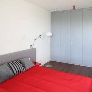 Sypialnię w bloku urządzono w bieli i szarościach. Czerwone dodatki dodają jej pazura. Projekt: Iza Szewc. Fot. Bartosz Jarosz.