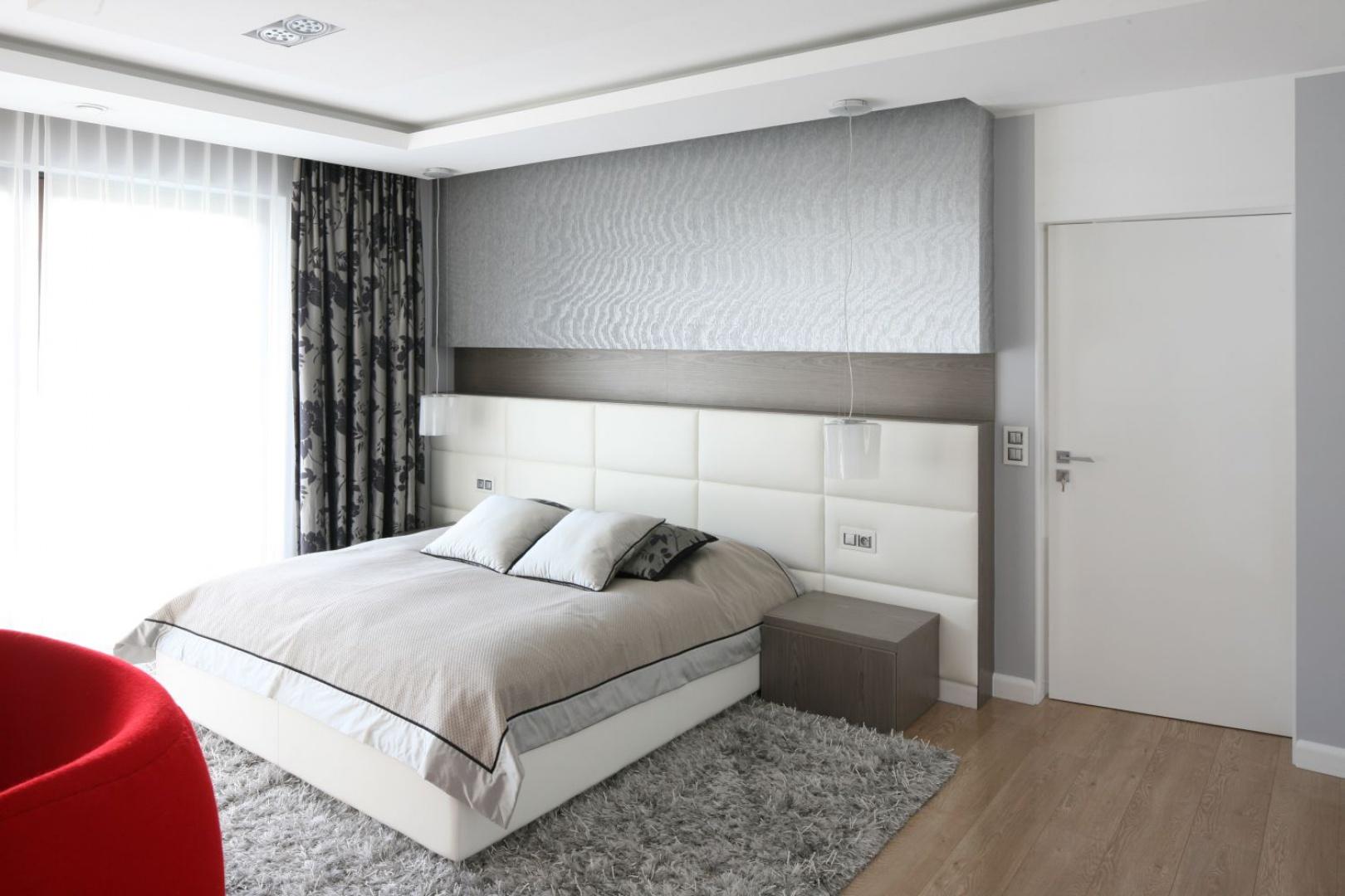Elegancką sypialnię urządzono w bieli i szarościach. Ten duet barw zdobi zarówno ściany, jak i łoże z tapicerowanym wezgłowiem. Projekt: Agnieszka Hajdas-Obajtek. Fot. Bartosz Jarosz.